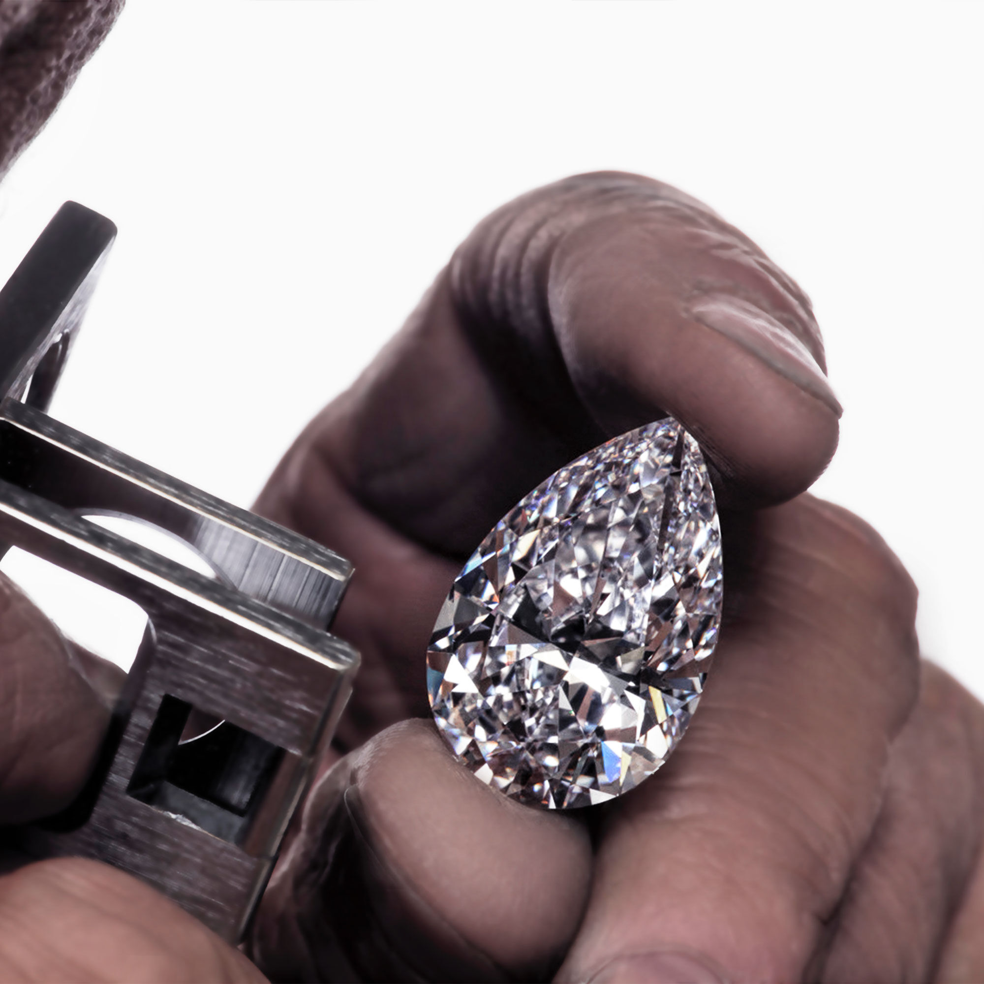 Close up of a Graff craftsman investigating a pear shape diamond through a loupe