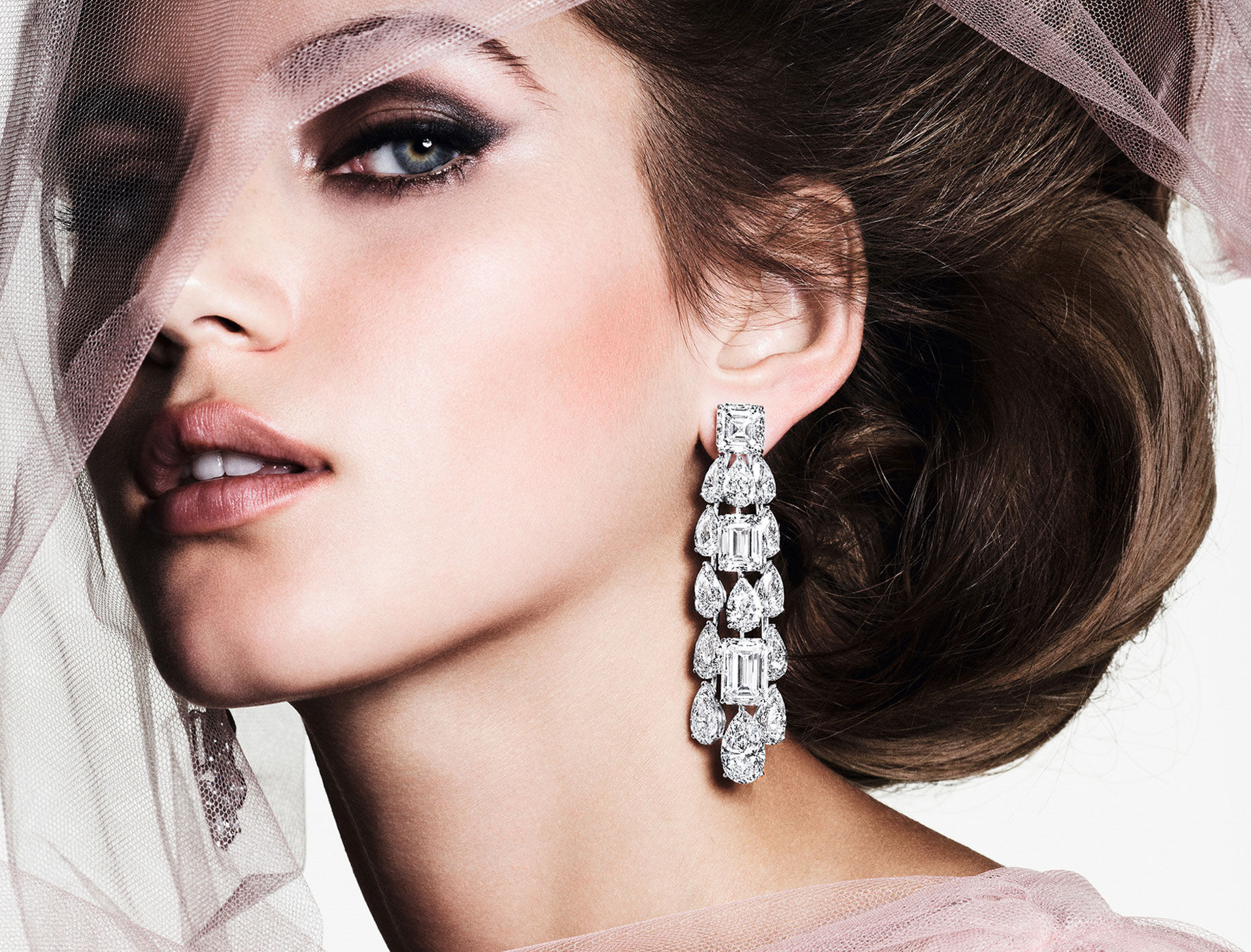 Close up of a model wearing Graff high jewellery white diamond earrings